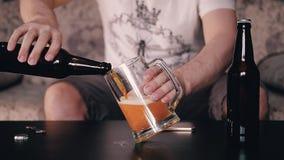 Der Mann nimmt Samen in einer Glasflasche und gießt ihn in einen Bierkrug, der auf dem Tisch steht stock video footage