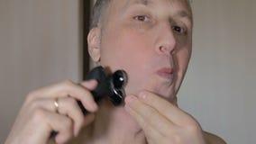 Der Mann rasiert sein Gesicht sauber mit einem Elektrorasierer nahaufnahme stock video footage
