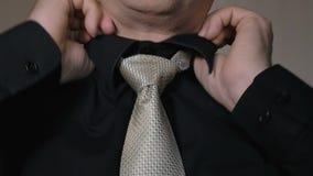 Der Mann richtet den Knoten seiner Bindung gerade Geschäftsmann, der geht, morgens zu arbeiten Schwarzes Hemd stock video
