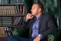 Der Mann-, ruhige und überzeugtegeschäftsmann, der in einem Stuhl, Bibliothek sitzt Lizenzfreies Stockbild