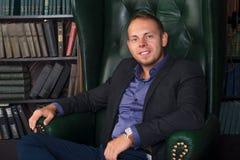 Der Mann-, ruhige und überzeugtegeschäftsmann, der in einem Stuhl, Bibliothek sitzt Stockbild