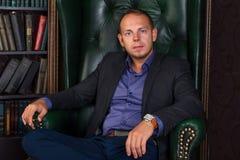 Der Mann-, ruhige und überzeugtegeschäftsmann, der in einem Stuhl, Bibliothek sitzt Stockfotografie