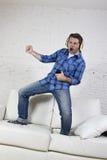 der Mann 20s oder 30s sprang auf Couch hörend Musik am Handy mit den Kopfhörern, die Luftgitarre spielen Lizenzfreies Stockfoto
