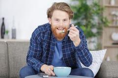 Der Mann sa? auf Sofa essend von der Sch?ssel lizenzfreies stockfoto