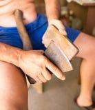 Der Mann schärft eine Axt mit einem Bleistiftspitzer Lizenzfreie Stockfotos