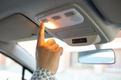 Der Mann schaltet das Licht auf der Decke im Auto ein Lizenzfreies Stockbild