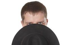 Der Mann schließt den unteren Teil des Gesichtes ein Hut. lizenzfreie stockfotos