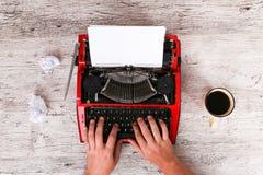 Der Mann schreibt auf einer Schreibmaschine, nahe bei der ein Tasse Kaffee ist lizenzfreie stockfotografie