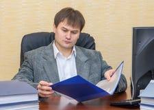 Der Mann am Schreibtisch im Büro, das einen Ordner mit Dokumenten hält stockfotografie