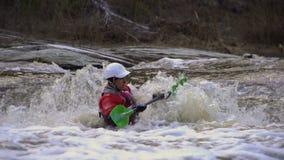 Der Mann schwamm hinunter den Fluss in einem Kajak