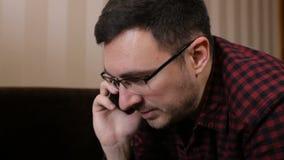 Der Mann schwört am Telefon, das auf einem Sofa liegt stock video