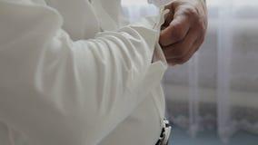 Der Mann setzt an Manschettenknöpfe auf ein weißes Hemd stock video footage