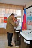 Der Mann setzt seinen Stimmzettel in den automatisierten Stimmzettel Lizenzfreies Stockbild