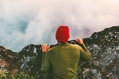 Der Mann, der sich auf der Randklippe über Wolken hinlegt, starren in Abgrund an Stockfoto