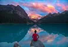 Der Mann sitzen auf Felsen Lake- Louisemorgenwolken mit aufpassend sich reflektieren Lizenzfreie Stockfotografie