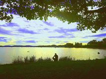 Der Mann sitzt über dem Wasser Stockbild