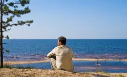 Der Mann sitzt auf dem Meer lizenzfreie stockfotos