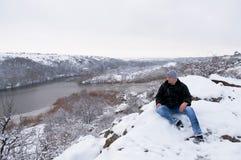 Der Mann sitzt auf einem snow-covered Felsen Lizenzfreie Stockfotos