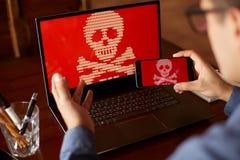 Der Mann sitzt nahe Laptop mit dem Telefon, das durch ransomware Spyware bitten um Geld blockiert wird und verschlüsselt ist Lapt Stockfotos