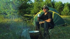 Der Mann in der Sonnenbrille sitzt am Zelt, trinkt Tee und passt den Werfer auf, über dem Feuer zu hängen stock footage