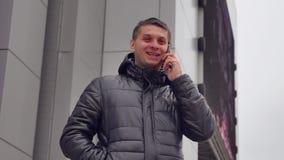 Der Mann spricht auf dem Telefon Smartphone Mann im Winter in einer Winterjacke spricht über einen Smartphone draußen stock video