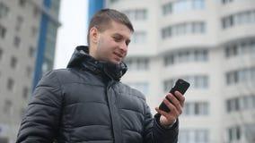 Der Mann spricht auf dem Telefon Smartphone Mann im Winter in einer Winterjacke spricht über einen Freienwolkenkratzer Smartphone stock footage