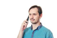 Der Mann spricht mit einem Bart durch stationäres Telefon Stockbild