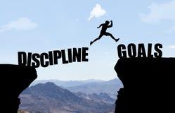 Der Mann springend über Abgrund mit Text DISCIPLINE/GOALS stockfotos