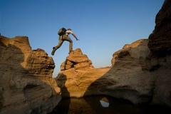 Der Mann springend über Felsen Stockbild