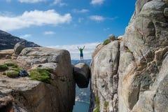 Der Mann springend über Kjeragbolten in Norwegen Kjerag lizenzfreie stockfotos