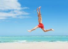 Der Mann springend auf den Strand Stockbilder
