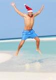 Der Mann springend auf den Strand, der Santa Hat trägt Stockfotografie