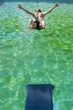 Der Mann springend in das Pool Stockbilder