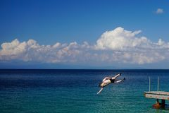 Der Mann springend in Meer vom Pier stockbilder
