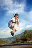 Der Mann springend mitten in einer Straße Stockbilder