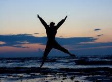 Der Mann springend nahe Meer. stockbilder