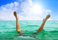 Der Mann springend in Ozean stockfotos