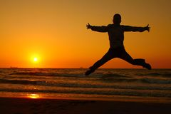 Der Mann springend in Sonnenuntergang Lizenzfreie Stockbilder