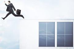 Der Mann springend weg vom konkreten Gebäude Stockfotos