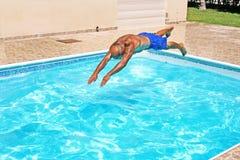 Der Mann springend zum Swimmingpool Stockfotografie