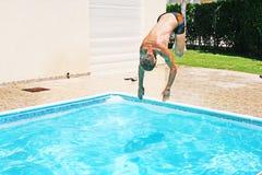 Der Mann springend zum Swimmingpool Lizenzfreie Stockfotografie