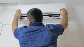 Der Mann steht unter der laufenden Klimaanlage und kühlt ab stock video footage