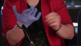 Der Mann am Tisch trägt Handschuhe, um einen Burger zu essen stock video
