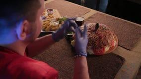 Der Mann am Tisch trägt Handschuhe, um einen Burger zu essen stock footage