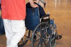 Der Mann trägt einen Behinderter in einem Rollstuhl stockbild