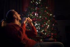 Der Mann träumt das Sitzen durch den Weihnachtsbaum Stockfoto