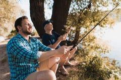 Der Mann und der alte Mann sitzen auf der Bank des Flusses auf Klappstühlen Sie halten die spinnings und das Fischen Lizenzfreies Stockbild
