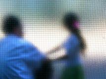 Der Mann und das Mädchen hinter Glas Lizenzfreie Stockfotografie