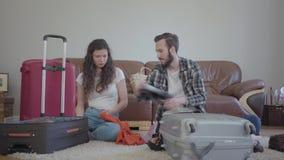 Der Mann und die Frau, die zu Hause auf dem Boden vor dem ledernen Sofa, einen Koffer vor Reise verpackend sitzt Der Ehemann stock video