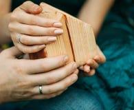 Der Mann und die weiblichen Hände, die ein kleines Haus halten Stockfoto